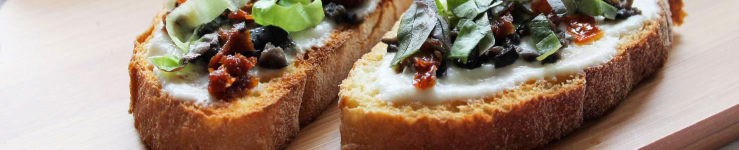 Bruschetta con cre,a di mozzarella, pomodorini secchi e olive