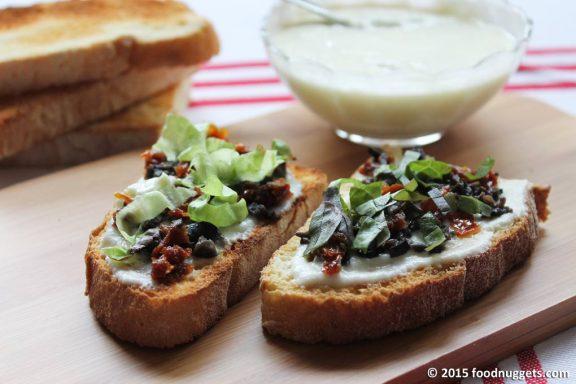 Bruschetta con crema di mozzarella, pomodorini secchi e olive