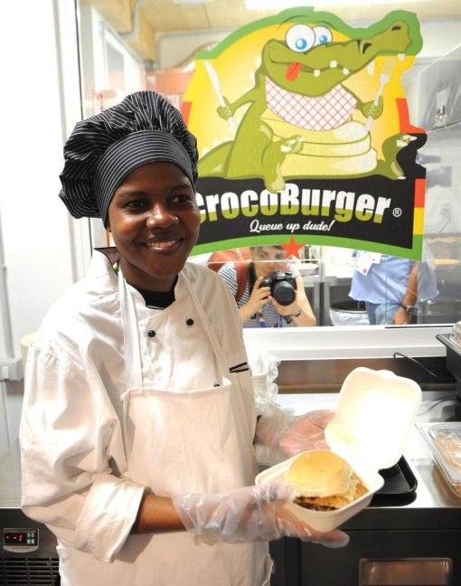 La cuoca mostra un Crocoburger