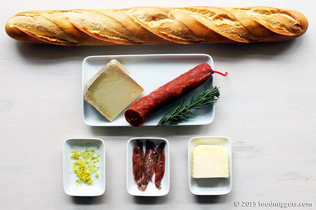 Baguette, pecorino toscano, salsiccia piccante, rosmarino, scorza di limone, acciughe sott'olio, burro
