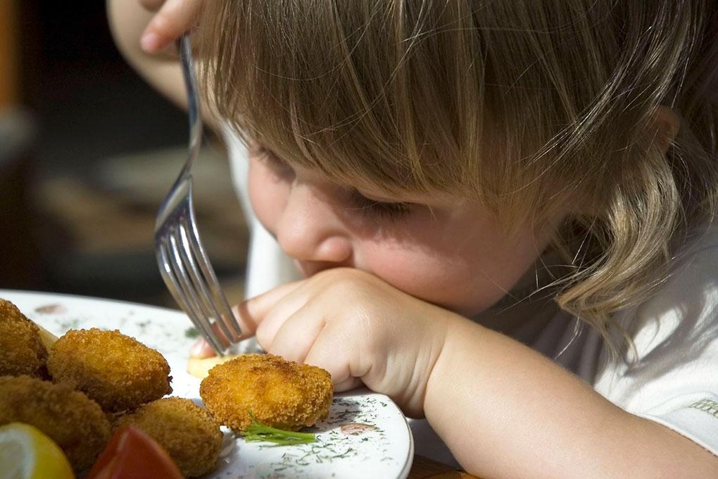Una bimba mangia le polpette di pollo